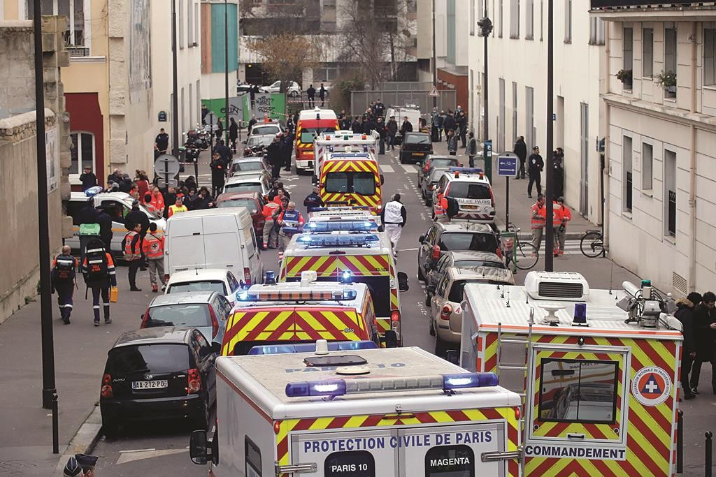 Ambulances gather outside the French satirical magazine Charlie Hebdo office, in Paris, Wednesday. (AP Photo/Francois Mori)