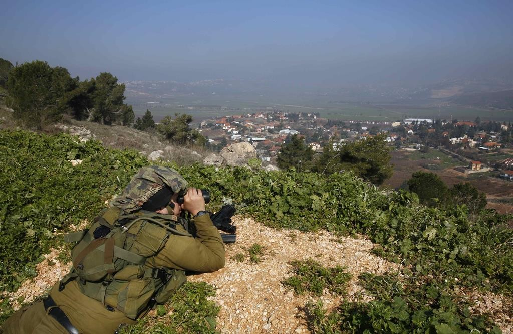 An Israeli soldier peering through binoculars towards the border with Lebanon from above the Israeli town of Metula on Tuesday. (REUTERS/Baz Ratner)