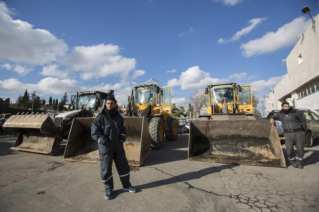 Yerushalayim Municipality Maintenance Department workers stand beside tractors for clearing snow, which is expected Wednesday. (Yonatan Sindel/Flash90)