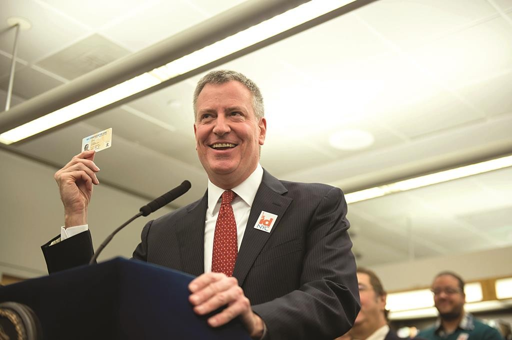 Mayor Bill de Blasio on Monday holds up a municipal identification card during a news conference at the Queens Public Library. (Demetrius Freeman/Mayoral Photography Office)