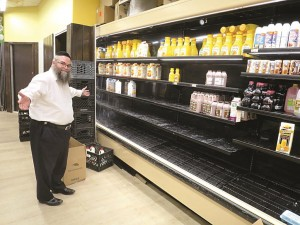 Parkville resident Yiddy Strohli looks for milk at the local grocer, but the shelves tell the story. (JDN )