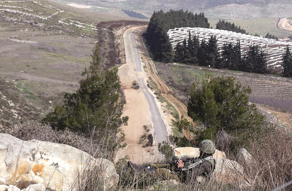An Israeli soldier keeps watch near the border with Lebanon on Monday. (REUTERS/Baz Ratner)