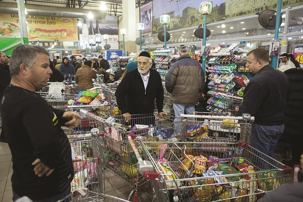 People standing at the checkout line in a Rami Levi supermarket in Yerushalayim on Tuesday. (Yonatan Sindel/Flash90)