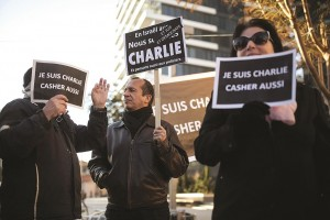 "People hold signs during a rally in Tel Aviv on Sunday in tribute to the victims of the shootings in Paris. The signs read, ""I am Charlie, and also kosher.""  (REUTERS/Baz Ratner)"