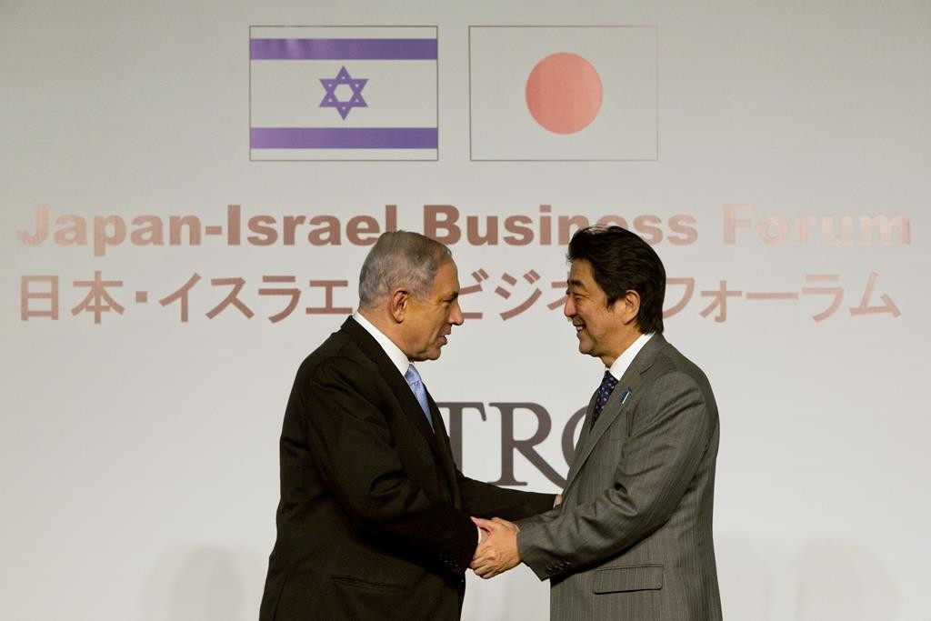 Japan's Prime Minister Shinzo Abe (R) shakes hands with Israeli Prime Minister Binyamin Netanyahu during a conference in Yerushalayim on Sunday.  (AP Photo/Sebastian Scheiner)