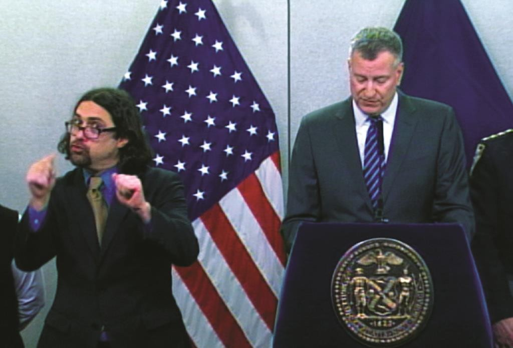Sign-language interpreter Jonathan Lamberton (L) on Monday translates during a news conference by Mayor Bill de Blasio. (AP Photo/Office of the Mayor)