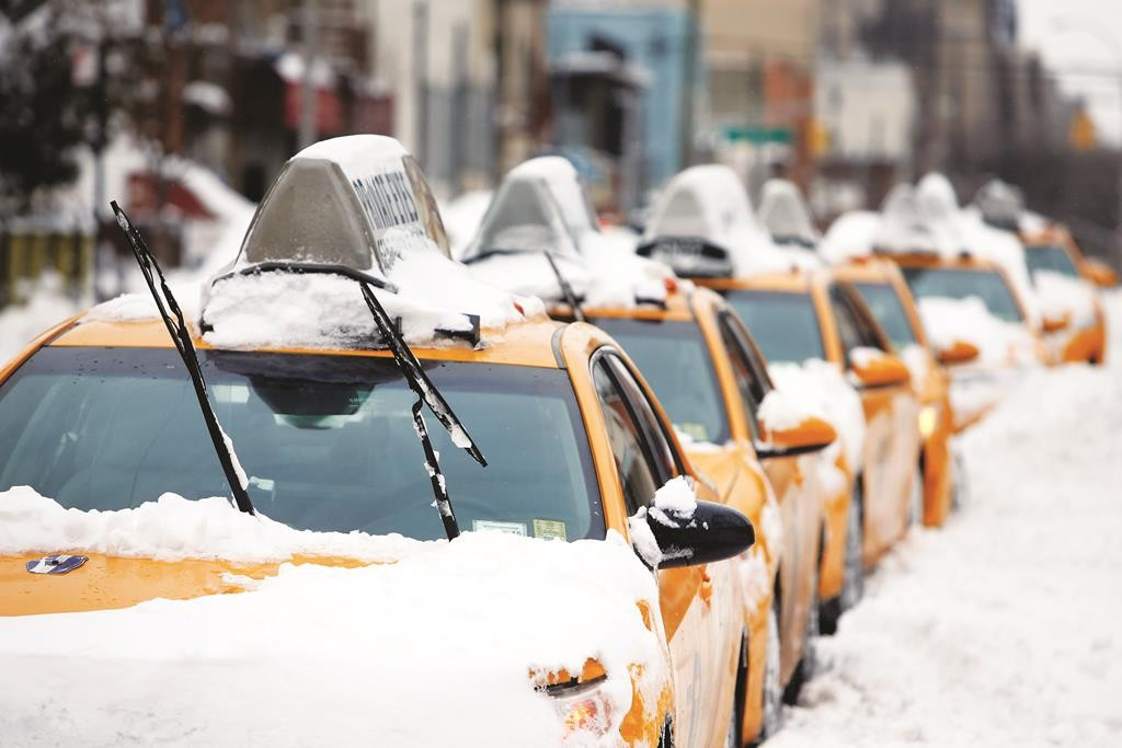Taxis stand idle Tuesday following the snow storm in Queens. (AP Photo/Jason DeCrow)