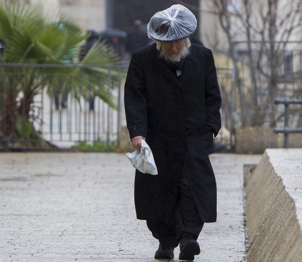 Walking in the rain near the Old City walls in Yerushalayim on Sunday. (Yonatan Sindel/Flash90)