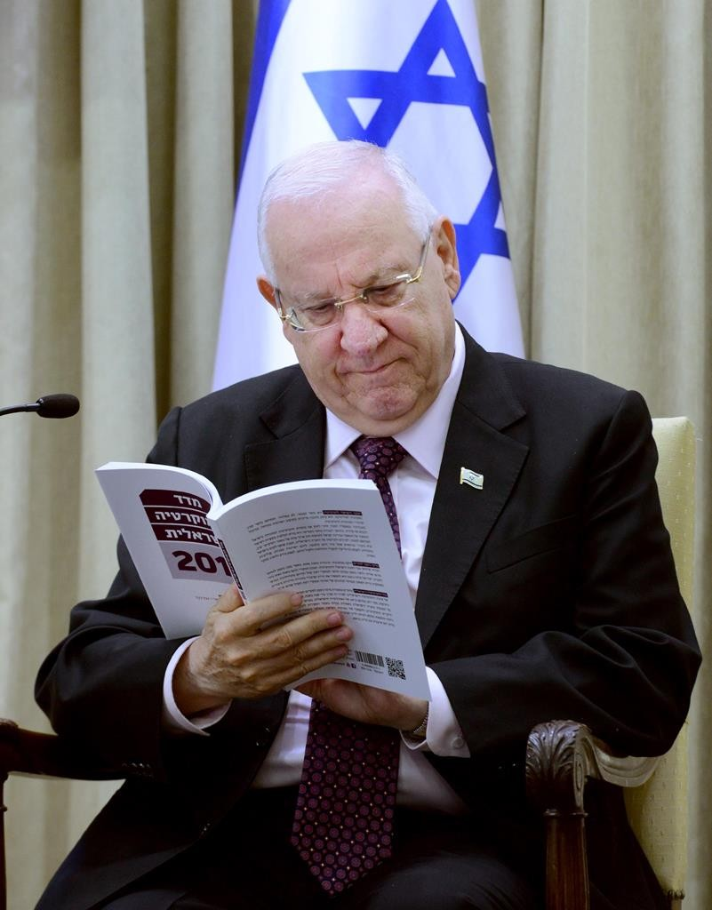 President of Israel Reuven Rivlin holding open the Israel Democracy Institute's Democracy Index for 2014 on Sunday.  (Mark Neyman / GPO)