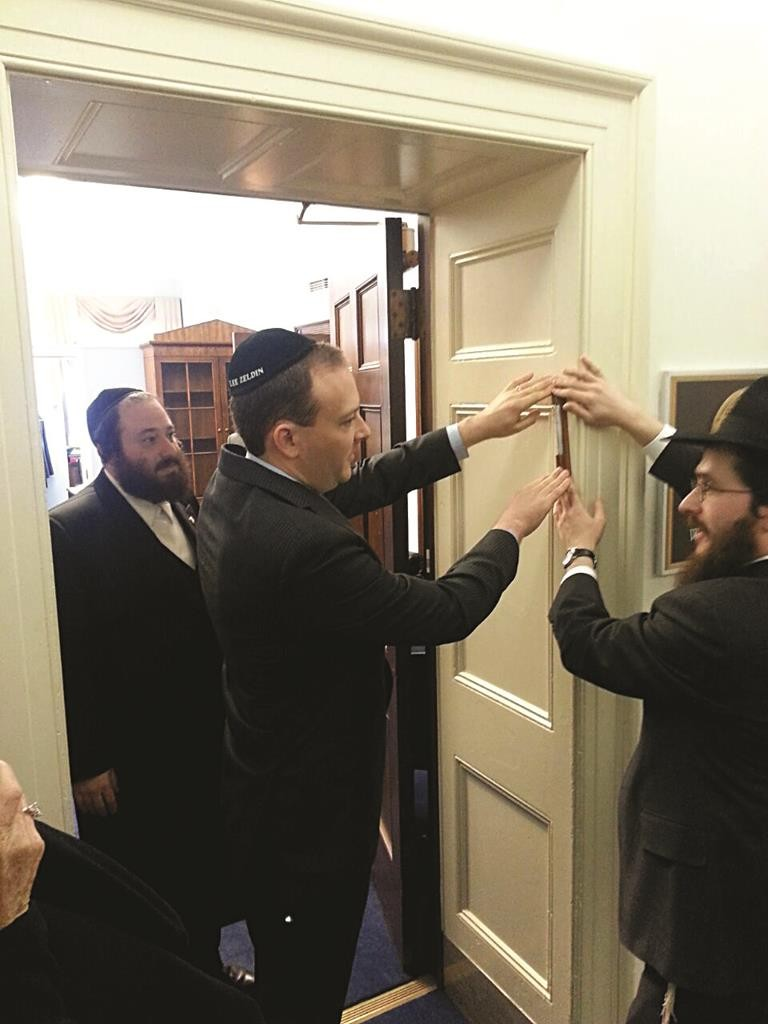 Rep. Lee Zeldin on Tuesday installs a mezuzah at his Capitol Hill office in Washington. At right is Rabbi Chaim Grossbaum of the Stony Brook Chabad center; at left is Rockland County Majority Leader Aron Wieder. (Hamodia Photo)