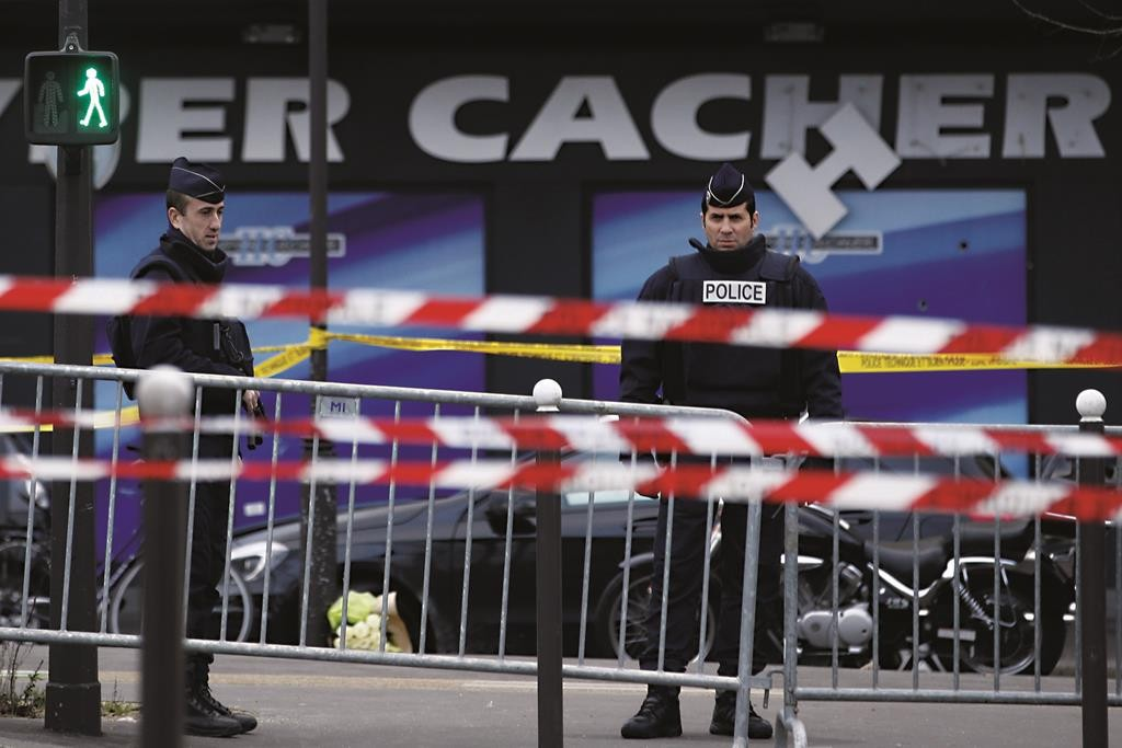 French police officers stand guard in front of the kosher grocery store in Paris, on Shabbos, a day after four people were killed. (KENZO TRIBOUILLARD/AFP/Getty Images)