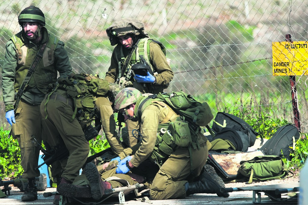 IDF soldiers tend to a comrade wounded in Wednesday's Hizbullah attack. (Basal Awidat/Flash90)