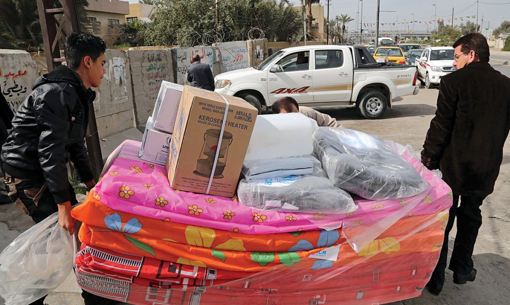 Displaced Iraqis who fled their town after the advance of Islamic terrorists in western Iraq receive humanitarian aid from a United Nations refugee agency, UNHCR, distribution center in the Mansour district of Baghdad, Iraq, Tuesday. (AP Photo/Karim Kadim)