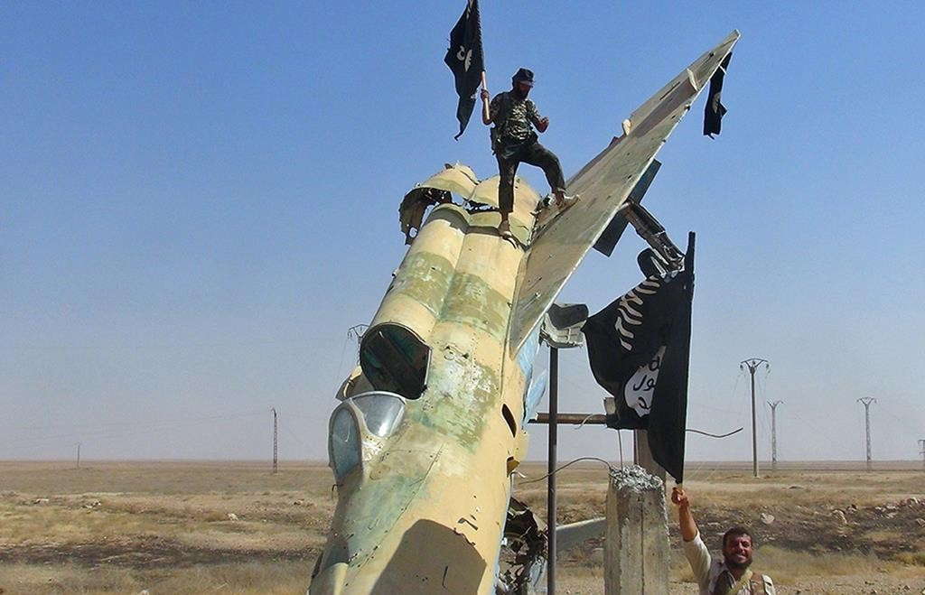 In this undated file photo, fighters of the Islamic State wave the group's flag from a damaged display of a government fighter jet following the battle for the Tabqa air base, in Raqqa, Syria.  (AP Photo/Raqqa Media Center of the Islamic State group)