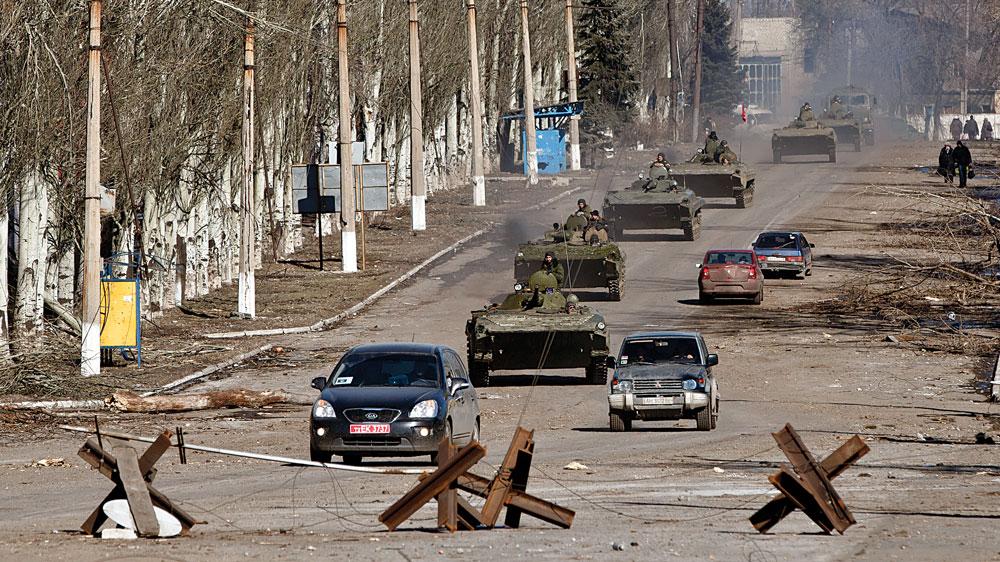 Russia-backed separatist drive a convoy of armored vehicles in Vuhlehirsk, near Debaltseve, Ukraine, Sunday.  (AP Photo/Vadim Ghirda)