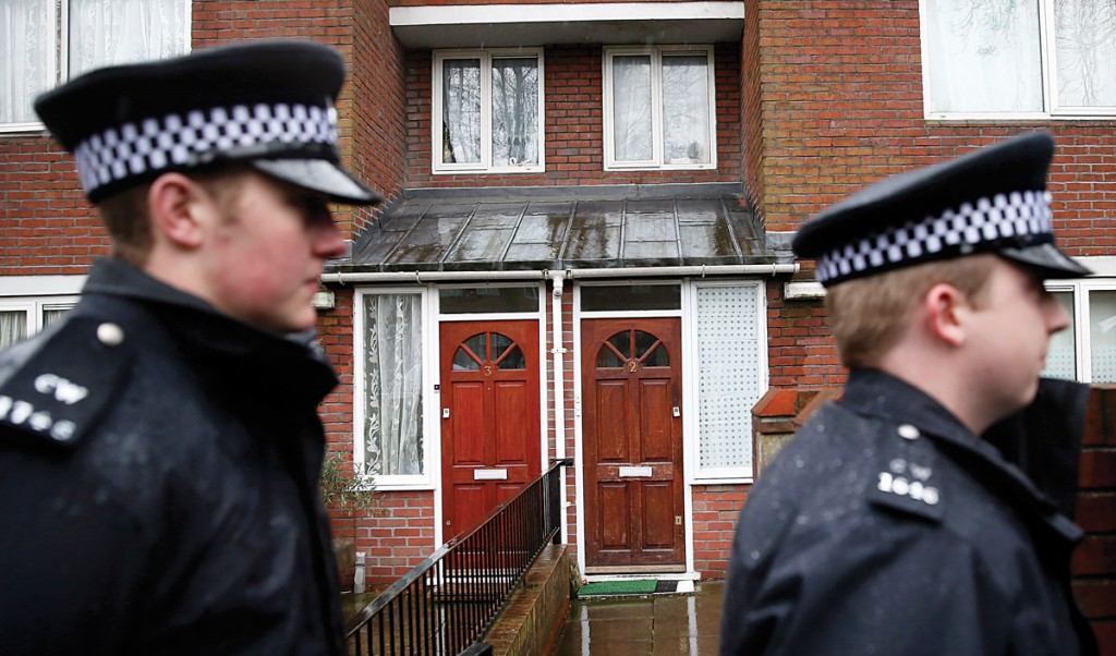 Two police officers walk outside a flat in London Thursday. Local media reported that the flat is the former home of Mohammed Emwazi. (REUTERS/Stefan Wermuth)