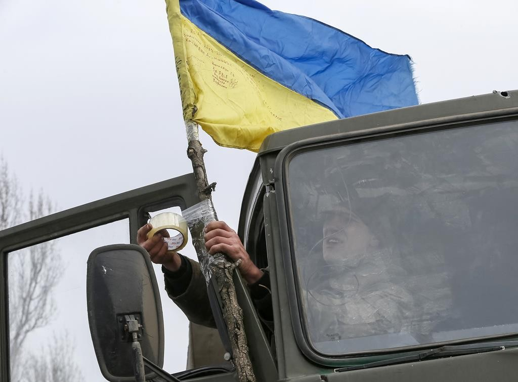A Ukrainian serviceman who fought in Debaltseve hoists a Ukrainian national flag to his vehicle before leaving for home, near Artemivsk Friday. (REUTERS/Gleb Garanich)