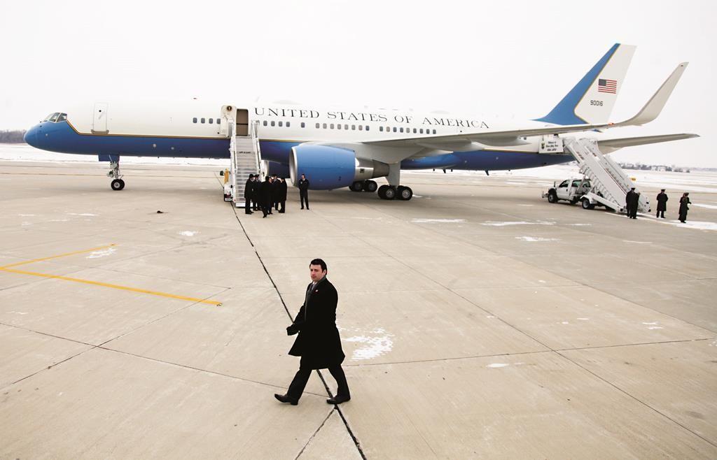 Secret Service members patrol the tarmac as Air Force One prepares to leave with President Barack Obama, Wednesday, Jan. 14, 2015, at Waterloo Regional Airport in Waterloo, Iowa. (AP Photo/Matthew Holst)