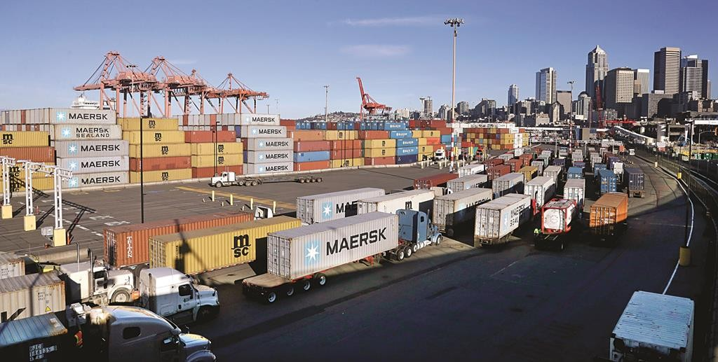 Loaded container trucks line up at a gate at the Port of Seattle Tuesday. (AP Photo/Elaine Thompson)
