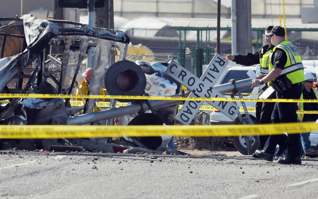 Police officers stand near a Metrolink train that hit a truck, left, and then derailed at a railroad crossing in Oxnard, California, on Tuesday, Feb. 24, 2015. (AP Photo/Mark J. Terrill)