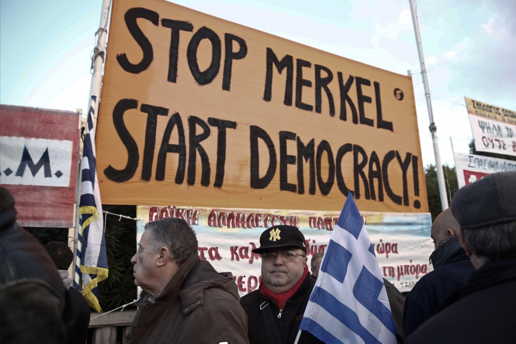 Pro-government protesters support the newly elected government's push for a better deal on Greece's debt at a rally in central Athens on Sunday, Feb. 15, 2015. (AP Photo/Petros Giannakouris)