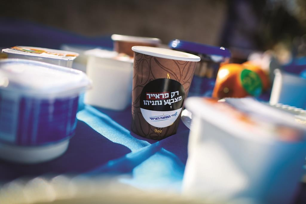 "A Zionist Camp breakfast in front of Prime Minister Binyamin Netanyahu's home, in Yerushalayim on Tuesday, was adorned by coffee cups with stickers saying ""Only a freier will vote for Bibi."" (Hadas Parush/Flash90)"