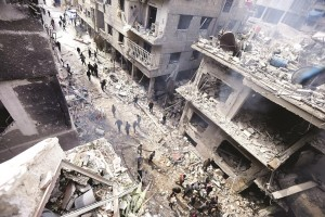 People inspect a site hit by what activists said were airstrikes by forces loyal to Syria's President Bashar al-Assad in the Douma neighborhood of Damascus, on Monday. (REUTERS/ Bassam Khabieh)