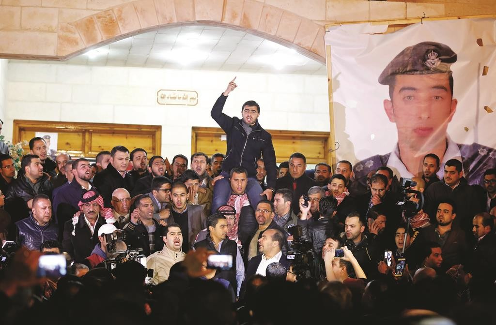 Supporters and family members of Jordanian pilot Lt. Muath al-Kaseasbeh express their anger over his reported killing, at the tribal gathering chamber, Amman, Jordan, Tuesday. (AP Photo/Raad Adayleh)