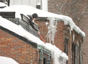A resident shovels snow from the roof of a Beacon Hill home Monday, in Boston.  (AP Photo/Steven Senne)