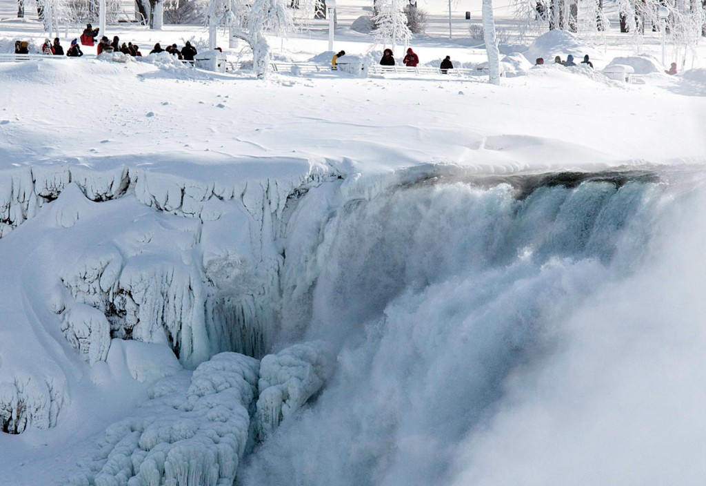 Visitors on Thursday look over masses of ice formed around the American Falls in Niagara Falls. (AP Photo/The Canadian Press, Aaron Lynett)