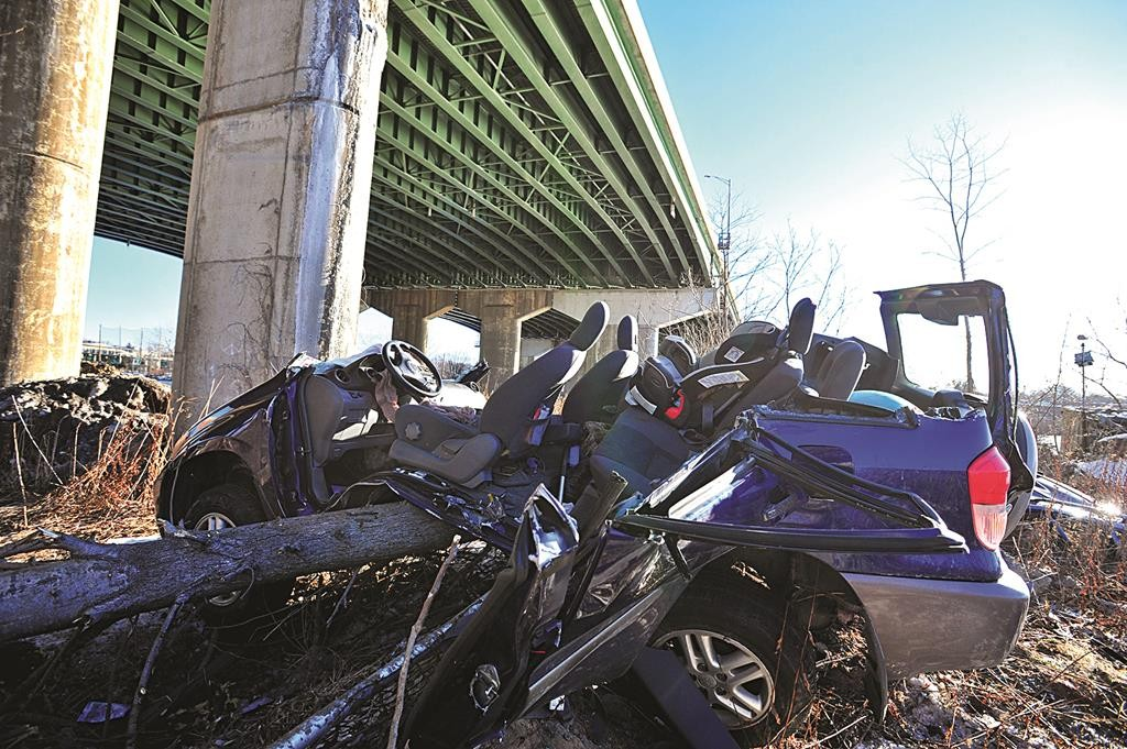 A SUV that catapulted off an I-80 bridge overhead lies Friday in a heap along the banks of the Hackensack River. (AP Photo/The Record, Marko Georgiev)