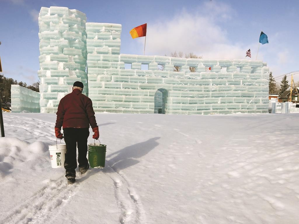 Dean Baker on Sunday carries buckets with water and ice for construction of the Hotel Saranac ice palace. The ice palace is part of the upcoming Saranac Lake Winter Carnival, held annually in Saranac Lake, NY. (AP photo)