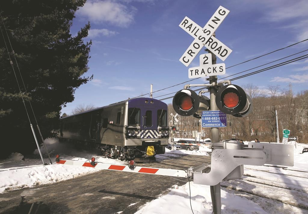 A train on Thursday passes through the intersection where an SUV was struck by a Metro-North train in Valhalla, N.Y., while emergency personnel remove the wreckage of the SUV. (AP Photo/Seth Wenig-Jason DeCrow)