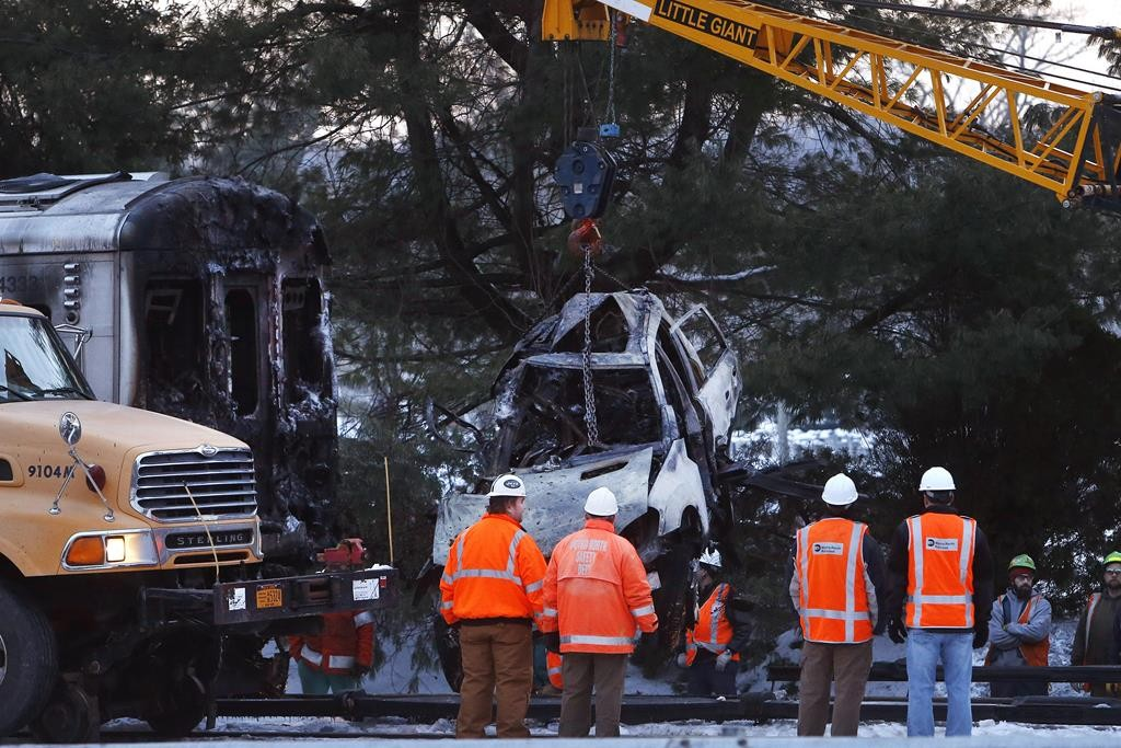 Emergency personnel on Thursday remove the wreckage of the SUV that was struck by a Metro-North train in Valhalla, N.Y. (AP Photo/Seth Wenig-Jason DeCrow)
