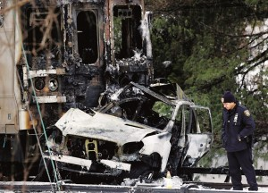 An investigator next to an SUV that was crushed and burned in front of a Metro-North train, Wednesday. (AP Photo/Mark Lennihan)