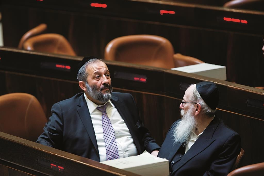 Shas chairman Aryeh Deri talking with United Torah Judaism MK Rabbi Yaakov Litzman in the Knesset recently. (Yonatan Sindel/Flash90)