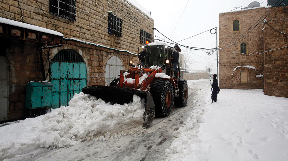 A bulldozer clearing snow in Chevron on Friday. (REUTERS/Mussa Qawasma)
