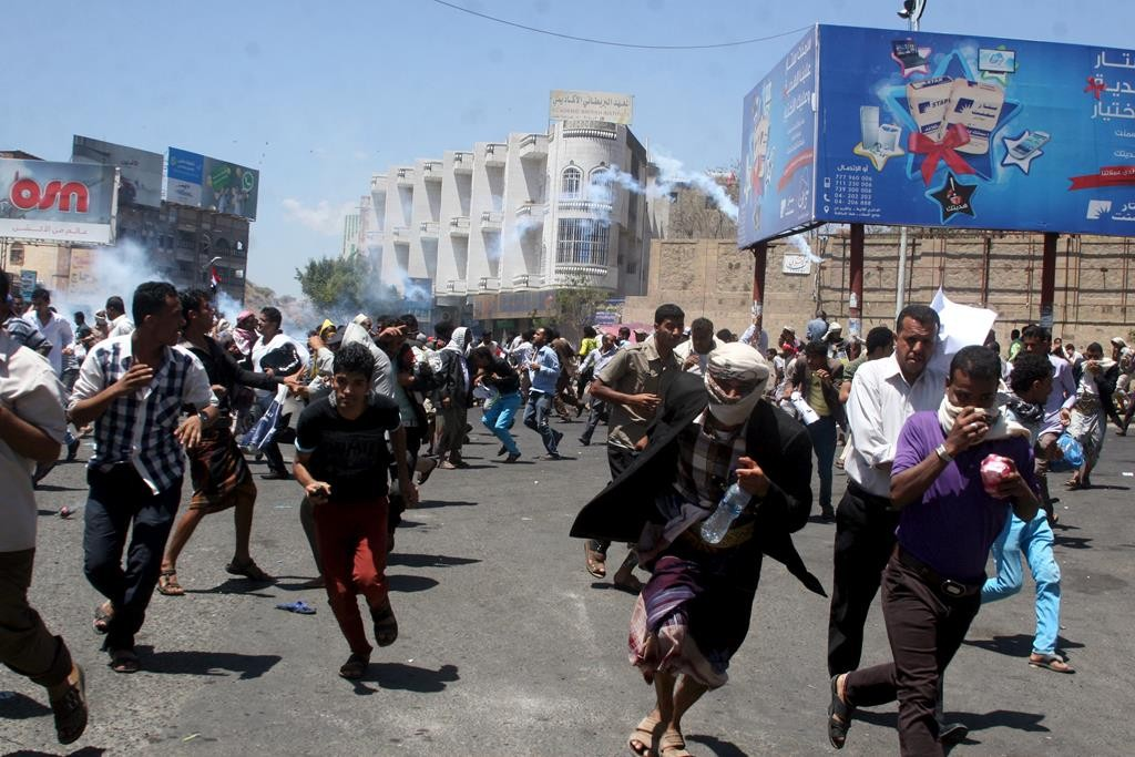 Anti-Houthi protesters run as pro-Houthi police troopers fire tear gas to disperse them in Yemen's southwestern city of Taiz Sunday. (REUTERS/Anees Mahyoub)