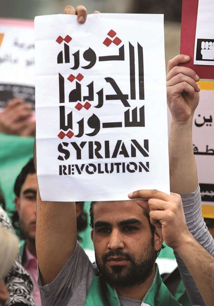 """An anti-Syrian government protester holds an Arabic placard that reads: """"The freedom Syrian revolution"""" as he attends a protest to mark the 4th anniversary of the Syrian uprising, at the Martyrs Square in downtown Beirut, Lebanon. (AP Photo/Hussein Malla)"""
