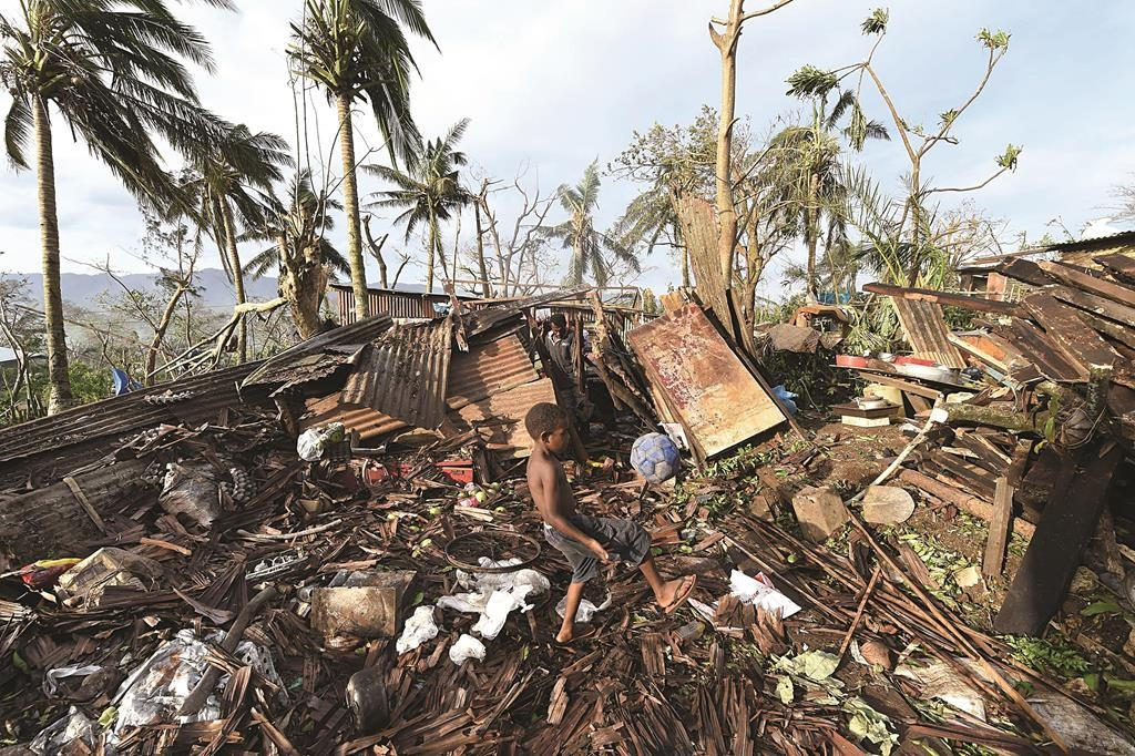A boy kicks a ball outside his destroyed family home, as his father, at back, picks through the debris in Port Vila, Vanuatu, in the aftermath of Cyclone Pam, Monday. (AP Photo/Dave Hunt, Pool)