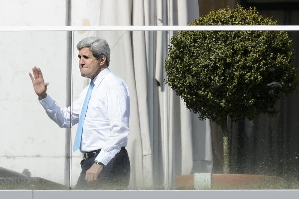 Secretary of State John Kerry,waves outside the hotel during a break from a bilateral meeting with Iranian Foreign Minister Mohammad Javad Zarif for a new round of Nuclear Talks, in Lausanne, Switzerland, Wednesday. (AP Photo/Keystone,Laurent Gillieron)