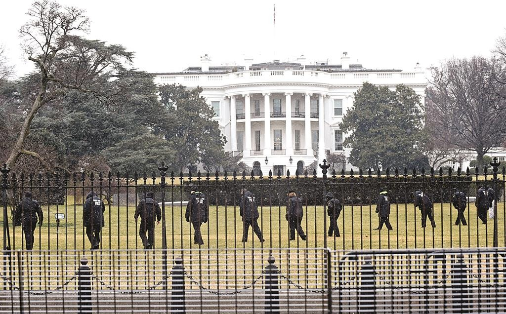 Secret Service officers search the south grounds of the White House in Washington, Monday, Jan. 26. A device, possibly an unmanned aerial drone, was found on the White House grounds during the middle of the night while President Obama and the first lady were in India. (AP Photo/Susan Walsh)