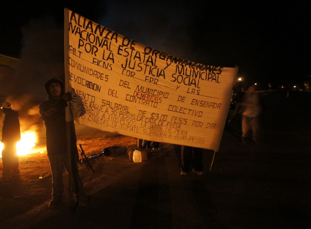 """In this March 18, 2015 photo, day laborers from the Valle de San Quintin protest on the side of the main highway near the communal land """"Gustavo Diaz Ordaz"""" in the municipality of Ensenada, south of Tijuana in Baja California, Mexico. Workers from about 60 farms in the area walked off their jobs on March 16 to demand better pay and labor conditions. (AP Photo/Omar Millan)"""