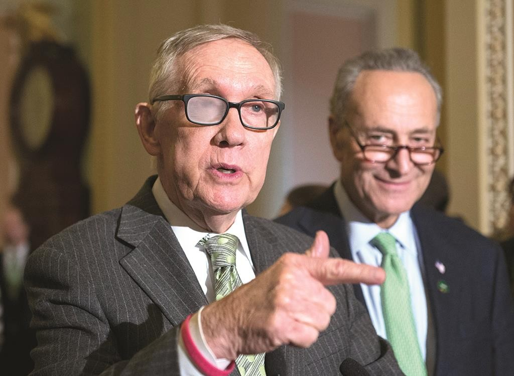 Senate Minority Leader Harry Reid of Nev., accompanied by Sen. Charles Schumer (D-N.Y.), speaks to reporters on Capitol Hill in Washington, Tuesday, March 17, following a policy luncheon. (AP Photo/Molly Riley)