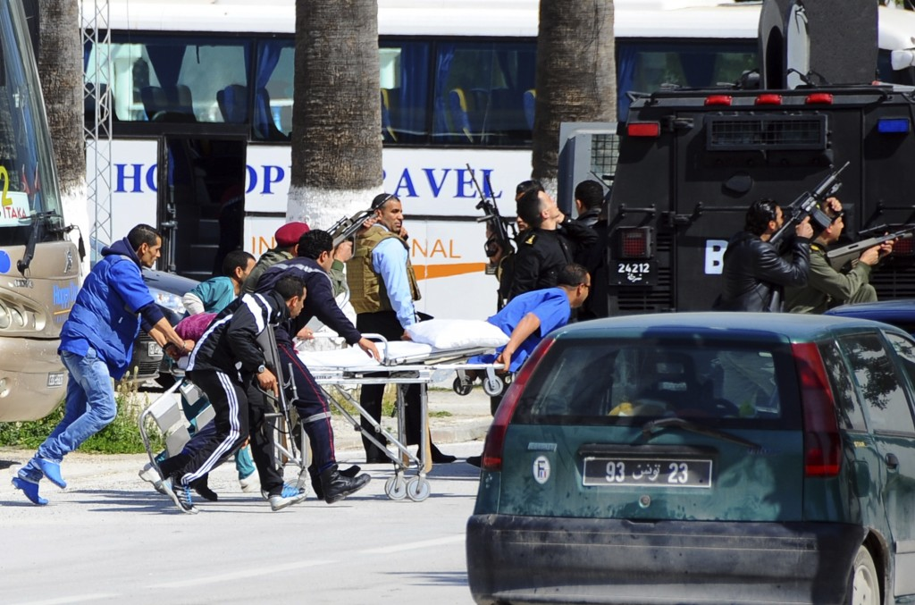 Escorted by security forces, rescue workers pull an empty stretcher outside the Bardo museum Wednesday in Tunis, Tunisia.  (AP Photo/Salah Ben Mahmoud)