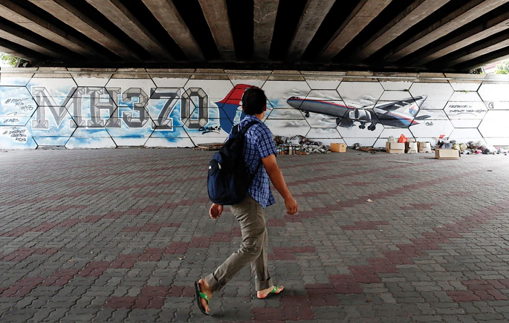 A man walks past graffiti depicting the missing Malaysia Airlines flight MH370 on the one-year anniversary of its disappearance in Kuala Lumpur, on March 8. (REUTERS/Olivia Harris)