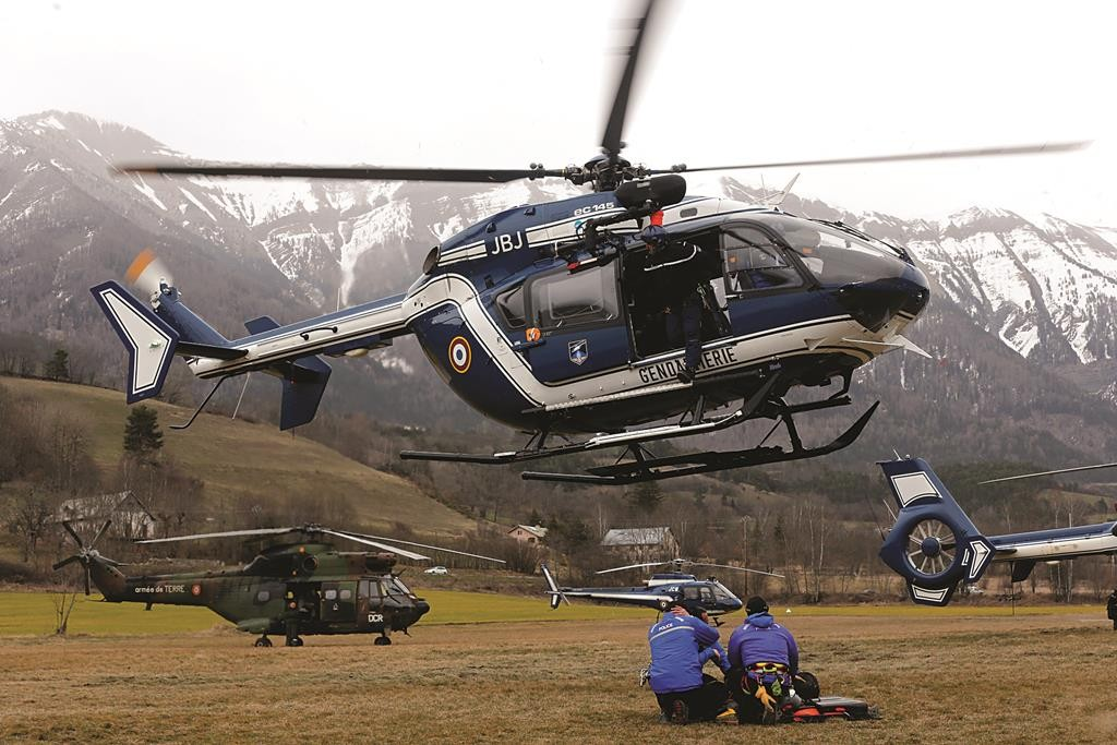 A helicopter of the French Gendarmerie hovers above an alpine field where forces gather during a rescue operation near the crash site of an Airbus A320, near Seyne-les-Alpes, Tuesday.  (REUTERS/Jean-Paul Pelissier)