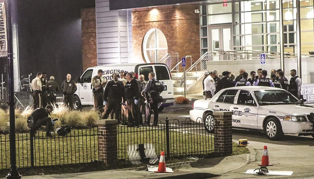 Police officers are gathered outside Ferguson Police Headquarters. Two officers were hit by gunfire there during a civilian protest on Thursday. (REUTERS/Lawrence Bryant/St. Louis American)