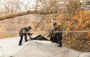 St. Louis County SWAT team prepare to search the attic of a house in Ferguson, Mo., Thursday,  following the shooting of two police officers.  (AP Photo/St. Louis Post-Dispatch, Christian Gooden)