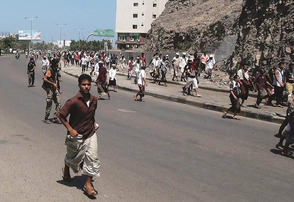 People flee after gunfire on a street in the southern port city of Aden, Yemen, Wednesday. Yemeni President Abed Rabbo Mansour Hadi fled, as Shiite rebels and their allies advanced on the city where he had taken refuge. (AP Photo/Yassir Hassan)